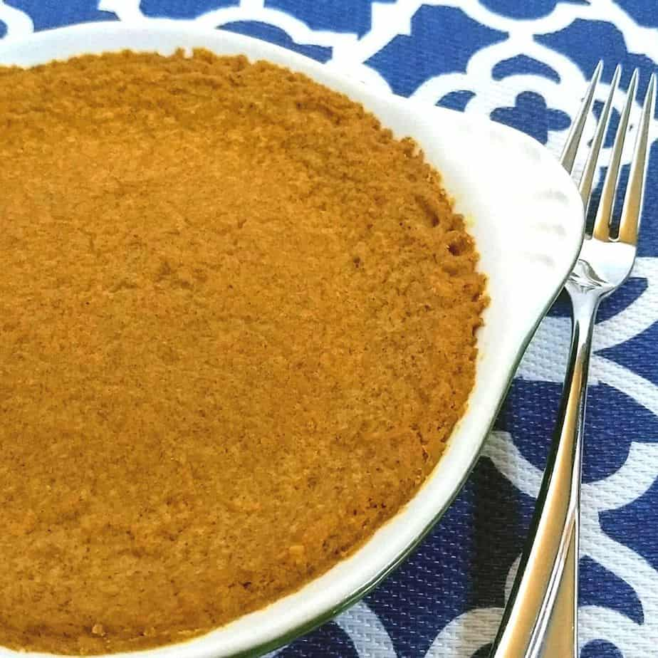 Pumpkin pie in dish with a fork on a blue and white mat