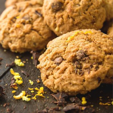 Cookies in a pile with orange zest and chocolate crumbs.