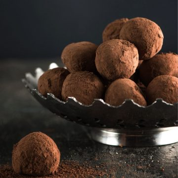Chocolate truffles in a silver bowl with 1 sitting on the table