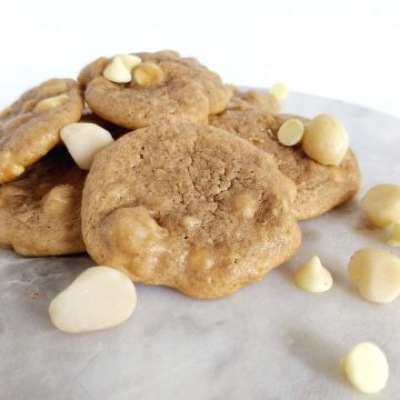 pile of cookies with macadamia nuts and white chocolate chips sprinkled on top