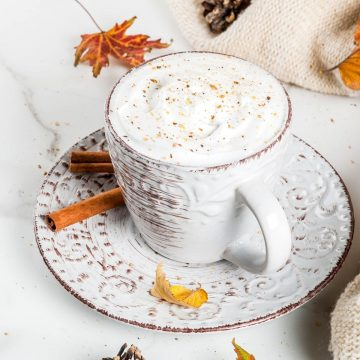 coffee in a white and brown cup with leaves and cinnamon sticks